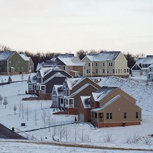 a row of houses with snow on the ground
